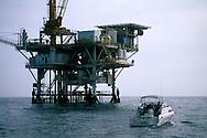 Recreational pleasure boat fishing next to oil drilling platform rig, Santa Barbara Channel, California Coast