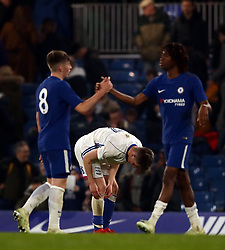 Birmingham City's George Baker is dejected as Chelsea celebrate their victory at the end of the match