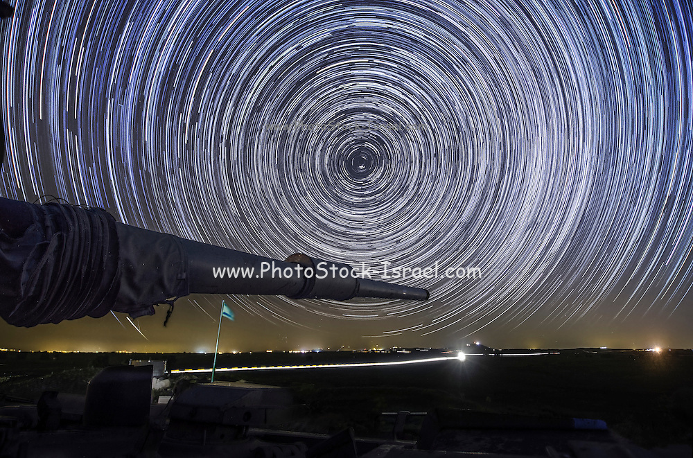 Time-exposure of polar star trails. The Pole Star, Polaris, is the short bright trail just off centre. The circular formation of the star trails is a result of the Earth's revolution in relation to the fixed stars. The different colours of the star trails results from the different intrinsic colours of the stars themselves, ranging from blue-white, through white and yellow, to orange. The photograph was taken at the Negev desert, Israel.