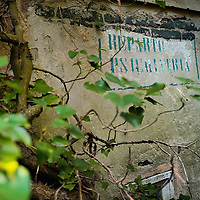 """VENICE, ITALY - AUGUST 27:  Sign """"Psychiatric Ward"""" seen at one of the entrances of the abandoned Hospital of Poveglia on August 27, 2011 in Venice, Italy. The island of Poveglia, with its ruined hospital and plague burial grounds, is said to be the most haunted location in the world. Though it is a multi-million dollar piece of real estate it lies deserted and off limits to the public. Its dark, forbidding shores are only minutes away from the glamour of the Venice Film Festival on the Lido. ..To discuss licensing our 4000 word photo documentary of the island, email robin@robinsaikia.com. ..British author Robin Saikia visited the site with Italian photographer Marco Secchi. Marco captured the sinister atmosphere of the island. Robin describes the terrifying apparitions and the stories behind them."""