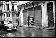 Old car passing in the street as it starts to rain.<br /> Image size 8x12, matted 16X20, edition of 10<br /> Gelatin Silver Print