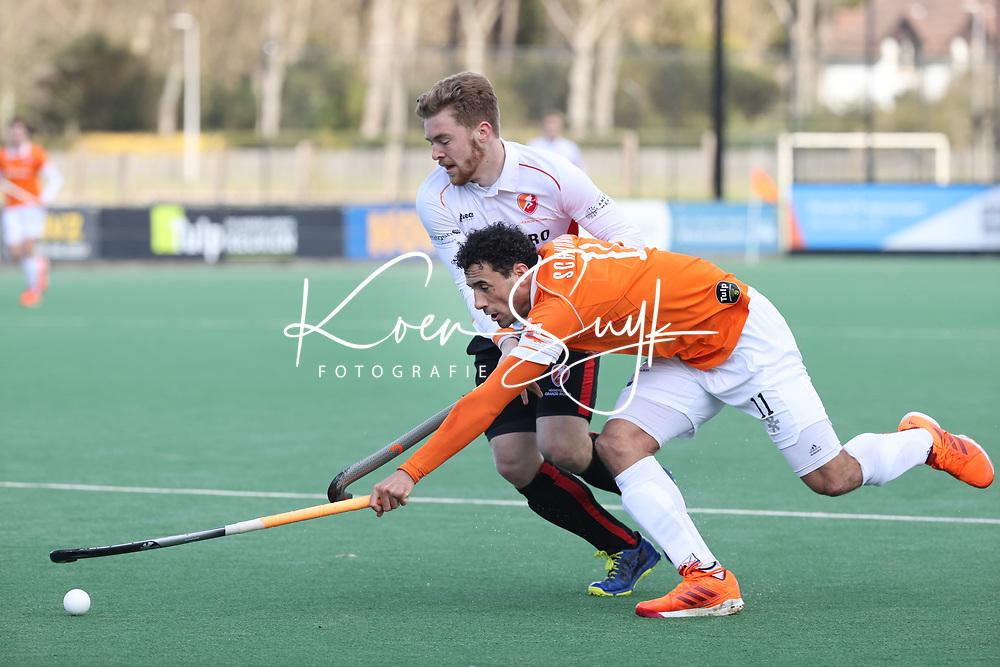 BLOEMENDAAL - Glenn Schuurman (Bldaal) met Jim van de Venne (Oranje Rood)   tijdens  de hoofdklasse hockeywedstrijd heren , Bloemendaal-Oranje Rood  (3-1).  COPYRIGHT  KOEN SUYK