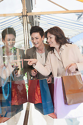 Two mature women looking in shop window with shopping bags, Bavaria, Germany