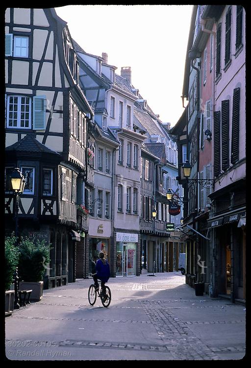 Girl rides bike past shops along cobblestone street in historic city center of Colmar, Alsace. France