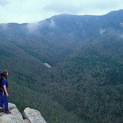 A hiker stands on the ledge with a view of the Franconia Ridge in the fog.  Old Bridle Path Trail, White Mtns, NH