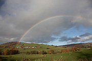 Rainbow over farmland and Welsh countryside near Rhayader, Powys, Wales, United Kingdom.