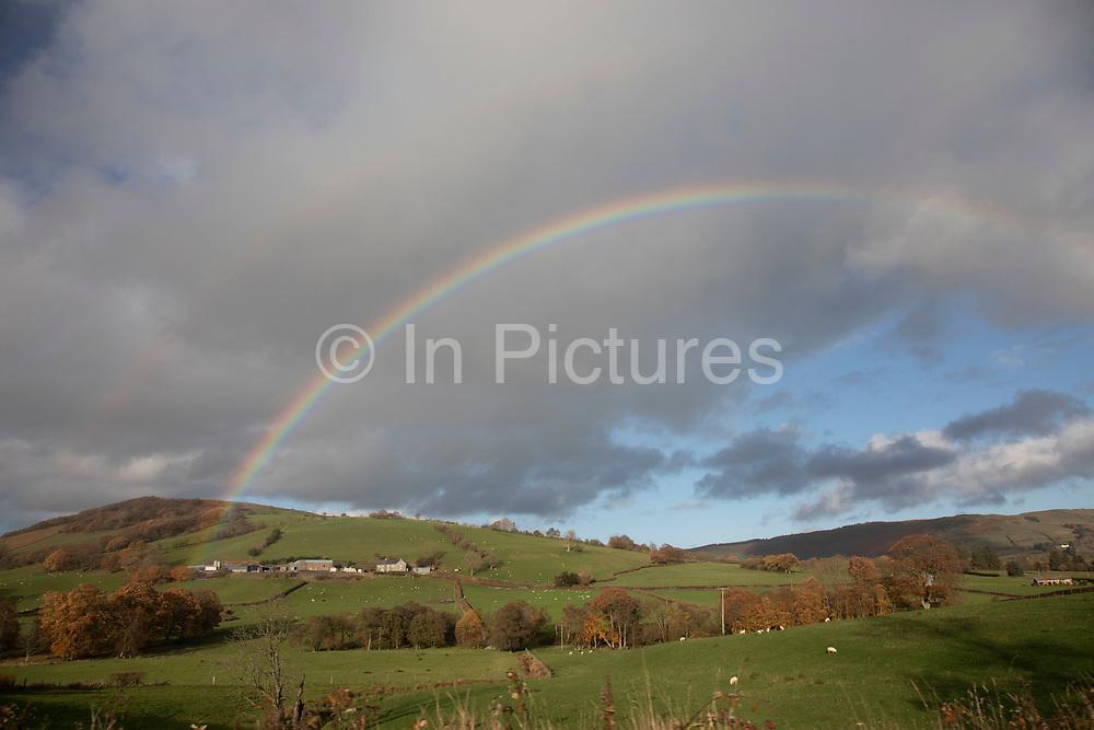 Rainbow over farmland and Welsh countryside near Rhayader, Powys, Wales, United Kingdom.