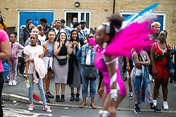 © Licensed to London News Pictures . 11/08/2018. Manchester , UK . People stand on pavements and cheer on people in the procession as is passes through Moss Side . The annual Moss Side Caribbean Carnival procession , celebrating dance , music and Afro-Caribbean culture , which passes in a loop from Alexandra Park and through the streets of Moss Side . Photo credit : Joel Goodman/LNP