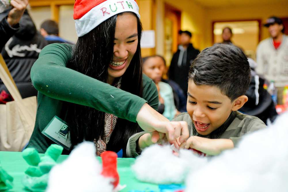 A volunteer works on crafts with a boy at the Goodwill Holiday Party at the Harrison Ave. location in Boston, MA.
