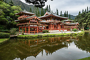 """The peaceful Byodo-In Temple reflects in a pond in Valley of the Temples Memorial Park, at 47-200 Kahekili Highway, Kaneohe, on the island of Oahu, Hawaii, USA. The Byodo-In Temple (""""Temple of Equality"""") was built in 1968 to commemorate the 100 year anniversary of the first Japanese immigrants to Hawaii. This Hawaii State Landmark is a non-practicing Buddhist temple which welcomes people of all faiths. The beautiful grounds at the foot of the Ko'olau Mountains include a large reflecting pond stocked with Japanese koi carp, meditation niches, and small waterfalls. Byodo-In Temple in O'ahu is a half-scale replica of the original Byodo-in Temple built in 1053 in Uji, Japan (a UNESCO World Heritage Site)."""