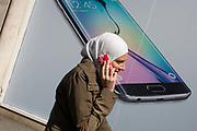 Phone user walks past Samsung shop window ad for new S6 model. Walking along the street in London's Soho, we see the women wearing a headscarf with her own handset to the ear - a call in progress. In the background is Samsung's latest smartphone model, being launched in all media this week in an attempt to win back users from a new iPhone range. Samsung Galaxy S6 and Samsung Galaxy S6 Edge are Android smartphones manufactured and marketed by Samsung Electronics. The S6 and S6 Edge jointly serve as successors to the Galaxy S5. The smartphones were officially unveiled in a press conference at Mobile World Congress on 1 March 2015.