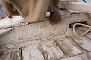 A detail of a crewman's foot with the peeling boards of his boat while sailing on the River Nile at Luxor, Nile Valley, Egypt. Feluccas are ancient Egyptian sail boats which were used in ancient times as a primary mode of transport and are the only type of boat that is still used extensively in the country. Plying this great African river is a cheap fare state-run ferry used by commuters and locals but these sailing boats serve tourists and therefore are the many victims of the tourism downturn. According to the country's Ministry of Tourism, European visitors to Egypt is down by up to 80% in 2016 from the suspension of flights after the downing of the Russian airliner in Oct 2015. Euro-tourism accounts for 27% of the total flow and in total, tourism accounts for 11.3% of Egypt's GDP.
