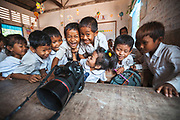 A group of schoolchildren laughing whilst watching a video of their class on a digital camera, Wat Chork Primary & Secondary School, Siem Reap, Cambodia