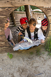 Girls dressed up as pirates watching a treasure map in adventure playground, Bavaria, Germany