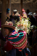 Local Quechua woman carrying flowers and clothes at Chinchero Town Sunday Market, Cusco region, Peru, South America