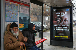 © Licensed to London News Pictures. 01/02/2021. London, UK. Commuters not socially distance sitting at a bus stop next to the government's 'Look him in the eyes - And tell him you always keep a safe distance.' awareness publicity campaign poster in north London.  Covid-19 infection rates are continuing to drop across London. According to a Government scientific adviser, the UK could be easing out of restrictions in March and back to almost normal by summer if vaccines are 70 to 80 per cent effective at blocking transmission. Photo credit: Dinendra Haria/LNP