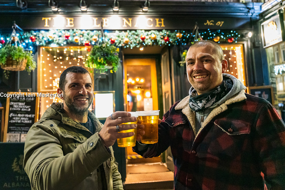 Edinburgh, Scotland, UK. 26 November 2020.Night views of Edinburgh as Christmas approaches.  Pictured; Paolo and Luigi from Italy enjoy a drink outside the Albanach pub on the Royal Mile in Edinburgh's Old Town.  Credit.  Iain Masterton/Alamy Live News