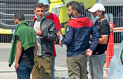©Licensed to London News Pictures 11/08/2020             Dover, UK. Migrants waiting to get on board a coach. Immigration officers processing illegal migrants at the port of Dover. These migrants have just been pick up by Border Force in the English Channel this morning. Photo credit: Grant Falvey/LNP