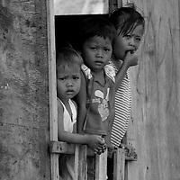 Children watch me pass through Gaya Island Water Village, Malaysia.