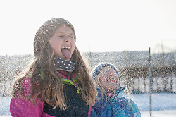 Girls sticking out tongue during snowfall