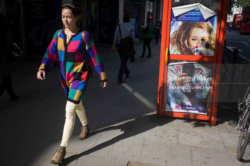 A woman pedestrian strides past a red phone kiosk advertising Natwest's online banking for students.