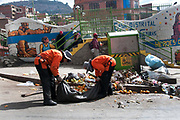 Bolivia June 2013. La Paz. Street market - women street cleaners, wearing orange uniforms,  clearing up after street market..