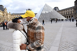 """Chinese tourists wear face mask as they kiss each other near the Louvre Museum in Paris, France, on January 28, 2020. An elderly Chinese tourist in a """"serious condition"""" in a Paris hospital is France's fourth confirmed case of the new coronavirus that has killed more than 100 people since it emerged in the Chinese city of Wuhan, France's top health official said Tuesday. Photo by Alain Apaydin/ABACAPRESS.COM"""