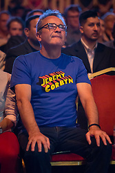 © Licensed to London News Pictures. 07/07/2016. LONDON, UK.  A Momentum supporter wearing a blue Jeremy Corbyn tee shirt at a rally in support of keeping Jeremy Corbyn as the Labour party leader at the Troxy in east London on 6th July 2016. The event was organised by Momentum, a group of Labour Party supporters who are campaigning for Jeremy Corbyn to remain as leader of the Labour Party, following the recent resignation of many shadow cabinet MP's and the growing likelihood of a Labour Party leadership challenge..  Photo credit: Vickie Flores/LNP