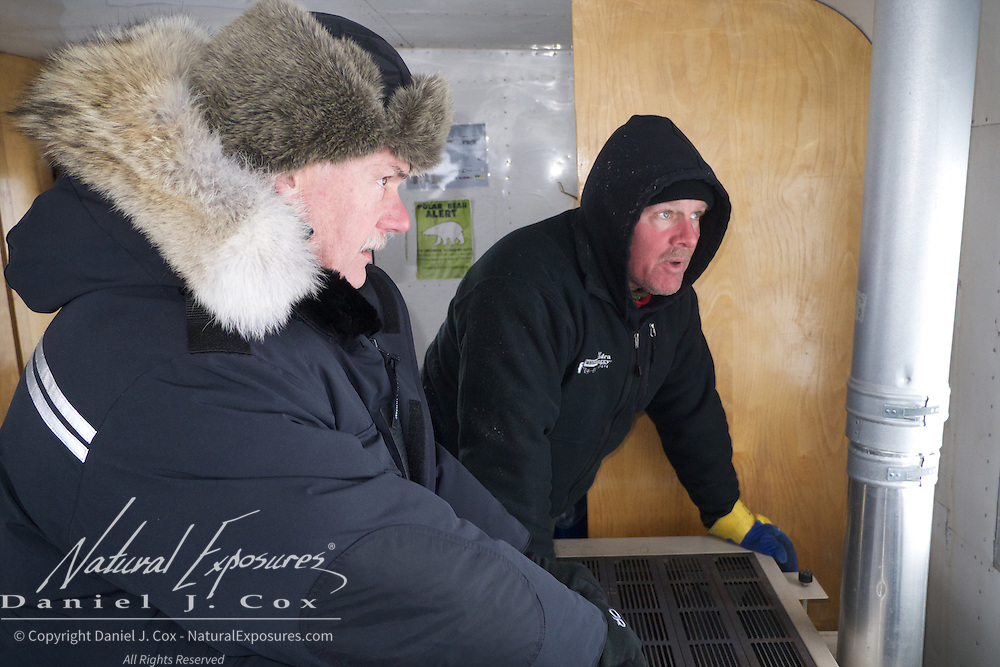 Daniel Smith and Kevin Burke warm their hands over the Tundra Buggy stove at Cape Churchill 2012