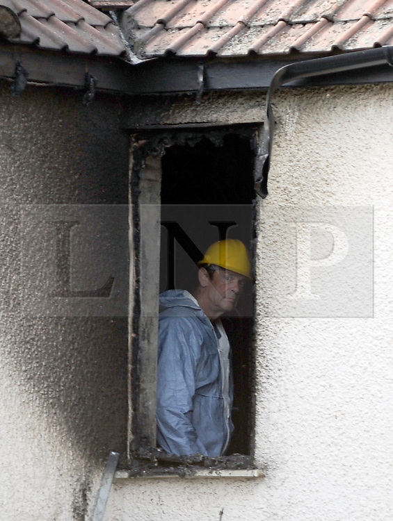 © Licensed to London News Pictures. 23/09/2011. LONDON, UK. An investigator looks out from a burnt upstairs window. Six people, including three children, two teenagers and an adult have died following a house fire in Neasden, North West London today (24 Sept 2011). Emergency services were called tot he blaze in the early hours of the morning. Photo credit:  Stephen Simpson/LNP