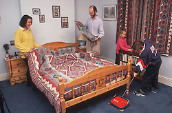 Family making bed and cleaning bedroom,