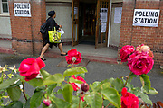 Seen through the Labour Party symbol red roses, a voter arrives at the polling station on the morning of the UK 2017 general elections outside St. Saviours Parish Hall in Herne Hill, Lambeth, on 8th June 2017, in London, England.