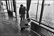 Nederland, Nijmegen 1-2-1995Tijdens historische hoge waterstand van de Waal probeert personeel van een cafe aan de Waalkade het interieur te redden. Hoogwater, milieu, klimaatverandering, overstromen, overstromingschade. Wateroverlast. februari 1995Eind januari, begin februari 1995 steeg het water van de Rijn, Maas en Waal tot record hoogte van 16,64 m. bij Lobith. Een evacuatie van 250.000 mensen was noodzakelijk vanwege het gevaar voor dijkdoorbraak en overstroming. op verschillende zwakke punten werd geprobeerd de dijken te versterken met zandzakken.Late January, early February 1995 increased the water of the Rhine, Maas and Waal to a record high of 16.64 meters at Lobith. An evacuation of 250,000 people was needed because of flood risk. At several points people tried to reinforce the dikes with sandbags.Foto: Flip Franssen