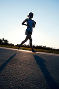 A female runner in barefoot shoes is silhouetted against the setting sun while running a city trail.