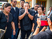 12 OCTOBER 2104 - BANG BUA THONG, NONTHABURI, THAILAND:  JATUPORN PROMPAN (center), a prominent Red Shirt leader, walks among supporters at the funeral rites for Apiwan Wiriyachai started at Wat Bang Phai in Bang Bua Thong, a Bangkok suburb, Sunday. Apiwan was a prominent Red Shirt leader, member of the Pheu Thai Party of former Prime Minister Yingluck Shinawatra, and a member of the Thai parliament. The military government that deposed the elected government in May, 2014, charged Apiwan with Lese Majeste for allegedly insulting the Thai Monarchy. Rather than face the charges, Apiwan fled Thailand to the Philippines. He died of a lung infection in the Philippines on Oct. 6. The military government gave his family permission to bring him back to Thailand for the funeral. He will be cremated later in October. The first day of the funeral rites Sunday drew tens of thousands of Red Shirts and their supporters, in the first Red Shirt gathering since the coup.   PHOTO BY JACK KURTZ