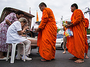 "21 JULY 2013 - BANGKOK, THAILAND:   An elderly woman sits in a chair to give monks alms at Wat Benchamabophit on the first day of Vassa, the three-month annual retreat observed by Theravada monks and nuns. On the first day of Vassa (or Buddhist Lent) many Buddhists visit their temples to ""make merit."" During Vassa, monks and nuns remain inside monasteries and temple grounds, devoting their time to intensive meditation and study. Laypeople support the monastic sangha by bringing food, candles and other offerings to temples. Laypeople also often observe Vassa by giving up something, such as smoking or eating meat. For this reason, westerners sometimes call Vassa the ""Buddhist Lent.""        PHOTO BY JACK KURTZ"