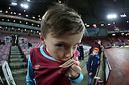 a Young West Ham fan kisses his badge on his West Ham shirt before the game. The Emirates FA cup, 4th round replay match, West Ham Utd v Liverpool at the Boleyn Ground, Upton Park  in London on Tuesday 9th February 2016.<br /> pic by John Patrick Fletcher, Andrew Orchard sports photography.