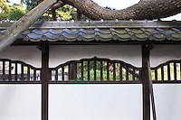 Japanese wall with a braced tree growing through it at Zenkoji Temple, Nagano