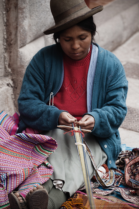 A peruvian andean women weaves a colorful hand dyed belt in downtown Pisac, Peru at the artisan market.