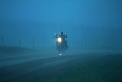 Storm Rider. North of Sturgis, SD. 1993<br /> <br /> Limited Edition Print from an edition of 50. Photo ©1993 Michael Lichter.<br /> <br /> The Story: The torrential downpour burst in the middle of a concert at a ranch in the hills just north of Sturgis.  Most people stayed put, but some went for it.  The rain turned to hail and and it hurt.  People laugh as they recall being caught like this and the feeling that goes with it.  Like getting punched in the face and wet going right to your core.  It's anything but funny when you're in it.