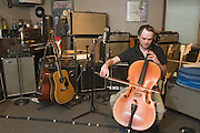 Tyler Morrison plays cello in the live recording room, Thursday, July 26, 2012, at Liquid Sound Studios in Greenville, Ind. Morrison, a percussionist for 27 years, has also played cello for 24 years, along with guitar and other instruments. (Photo by Brian Bohannon)