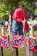 A Civil War re-enactor collects flags from grave sites following a ceremony marking Confederate Memorial Day at Magnolia Cemetery April 10, 2014 in Charleston, SC. Confederate Memorial Day honors the approximately 258,000 Confederate soldiers that died in the American Civil War.
