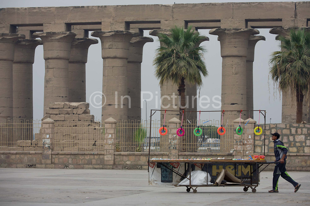 A trinkets stallholder pushes his cart towards arriving tourists in front of the ancient Egyptian columns of Luxor Temple, Luxor, Nile Valley, Egypt. Local businesses are obviously very dependent of the tourism industry and therefore badly affected by the downturn. According to the country's Ministry of Tourism, European visitors to Egypt is down by up to 80% in 2016 from the suspension of flights after the downing of the Russian airliner in Oct 2015. The temple behind was built by Amenhotep III, completed by Tutankhamun then added to by Rameses II. Towards the rear is a granite shrine dedicated to Alexander the Great and in another part, was a Roman encampment. The temple has been in almost continuous use as a place of worship right up to the present day.