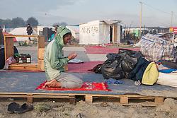 """Calais, Pas-de-Calais, France - 26.10.2016    <br />  <br /> A camp resident is praying in a former camp Mosque. Since the beginning of the governmental camp destruction on the day before many fires were placed by camp residents inside camp. Wide parts of the camp burned down. 3rd day of the eviction on the so called îJungle"""" refugee camp on the outskirts of the French city of Calais. Many thousands of migrants and refugees are waiting in some cases for years in the port city in the hope of being able to cross the English Channel to Britain. French authorities announced a week ago that they will evict the camp where currently up to up to 10,000 people live.<br /> <br /> Ein Campbewohner betet in einer ehemaligen Moschee des Camps. Seit dem Beginn der behoerdlichen Campzerstˆrung wurden zahlreiche Feuer im Camp gelegt. Weite Teile des Camps brannten ab. Dritter Tag der Raeumung des so genannte îJungleî-Fluechtlingscamp in der franzˆsischen Hafenstadt Calais. Viele tausend Migranten und Fluechtlinge harren teilweise seit Jahren in der Hafenstadt aus in der Hoffnung den Aermelkanal nach Groflbritannien ueberqueren zu koennen. Die franzoesischen Behoerden kuendigten vor einigen Wochen an, dass sie das Camp, indem derzeit bis zu bis zu 10.000 Menschen leben raeumen werden. <br /> <br /> <br /> / 261016"""