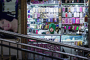 """A shot of a woman selling phone accessories in Kashgar, Xinjiang, China. The Xinjiang province is located in western China and named a """"Special Economic Zone in 2010. In the recent decades the centuries old architecture has been being slowly replaced and rebuilt with fortified concrete structures and surrounded by Chinese-style highrises."""