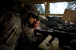 A sniper and officer with Charlie Co. 1-26 Infantry 1st Infantry Division watch with concern as a convoy passes near the Joint Security Station in central Adhamiya on Friday April 27, 2007
