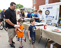 Chris Lemay with his sons Even and Braydon enjoy a hotdog from the Belmont Rotary Club during Belmont's National Night Out on Tuesday evening.  (Karen Bobotas/for the Laconia Daily Sun)