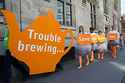 Human tea bags protest outside Sainsbury's AGM to highlight concern over supermarket's decision to replace Fairtrade tea on July 5th 2017 in London, United Kingdom. Campaigners dressed up as tea bags protest in front of a giant teapot as shareholders arrive for Sainsbury's annual general meeting. The human tea bags' message says 'Save Fairtrade Tea'. The stunt by Oxfam and CAFOD is part of a campaign launched by a coalition of charities.  One of the main concerns is that farmers and workers who produce 'Fairly Traded' tea for Sainsbury's will no longer have direct control over how they spend the premium – an additional payment on the basic price intended to benefit them. Instead, they will have to apply to a board set up by Sainsbury's in London. London. United Kingdom.