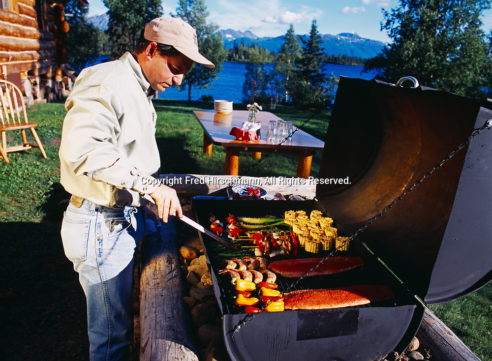 Steve Lacroix grilling salmon scallop shis kebobs, leeks, asparagus, shrimp, peppers and steaks, outdoors at Winterlake Lodge, Finger Lake, Alaska.