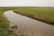 Buitendijks kweldergebied van waterschap Blija Buitendijks.<br /> Waterschap Blija Buitendijks is het kleinste waterschap van Nederland. Het waterschap beheert 100 hectare weiland, gelegen bij het dorp Blija in het noorden van Friesland, tussen de Waddenzeedijk en zomerdijk (links op de foto). Direct achter de 2,25 m +NAP hoge zomerdijk bevindt zich het uitgestrekte kweldergebied van de Waddenzee. Bij hoogwater (vloed) stroomt het buiten de zomerdijk gelegen kwelder regelmatig onder water. Bij extreem hoog water, bijvoorbeeld bij springtij en noordwesterstorm komt het zeewater vanuit de Waddenzee ook over de zomerdijk. De door het waterschap beheerde polder komt dan geheel onder water te staan, soms zelfs tot halverwege de Waddenzeedijk. Bij afgaand tij (eb) stroomt het zeewater via de klepstuwen in de zomerdijk terug naar de Waddenzee. De afgebeelde watergang (afwateringssloot) bevindt zich langs de zomerdijk met daarin de betonnen duiker met klepstuw.